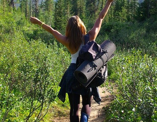 Glad kvinde på vandring med rygsæk